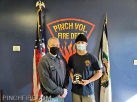 Firefighter Doug Douglas presenting his son Firefighter Hunter Douglas with his firefighter shield